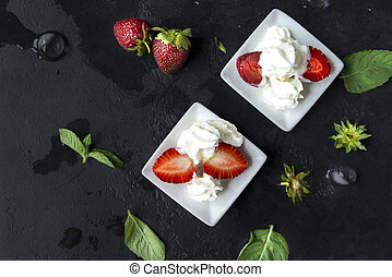 berries fresh strawberries with whipped cream on a black background