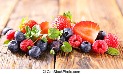 berries fruits and mint on wood background
