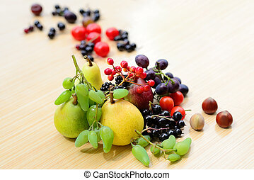 Berries, fruits, vegetables and nuts mixed on the table - ...