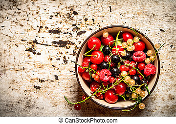 Berries in a Cup. On rustic background.