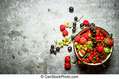 Berries in a Cup. On stone table.