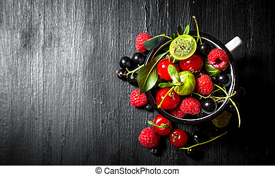 Berries in a mug. On black wooden background.