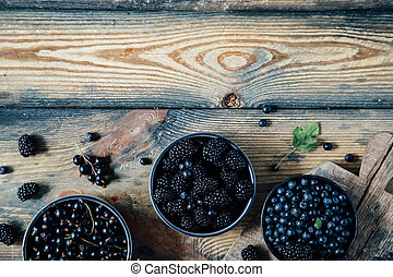 berries in bowls on a wooden background