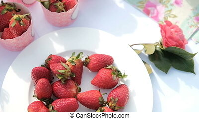Berries of strawberries on white plate on table indoors. ...