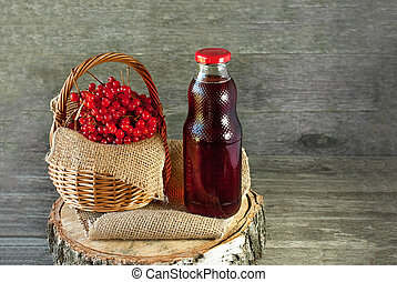 Berries of viburnum in a basket on a napkin next to the glass transparent bottle of juice. Rustic. Copy space