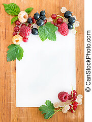 Berries on wooden background with paper for notes