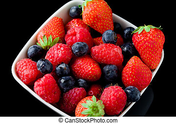 Berries - photo of mixed fresh berries on red lighted...