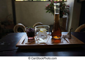 Berries tea with ice ball on wood background