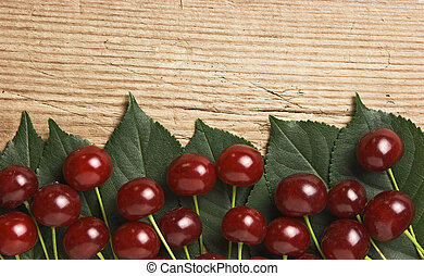 Berry Cherry with leaves on wooden background