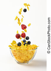berry fruit and corn flakes falling into bowl