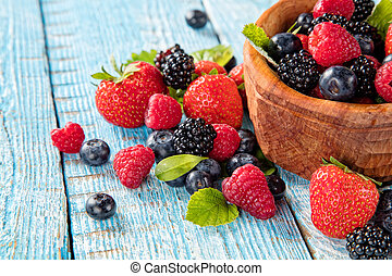Berry fruit in saucer placed on old wooden planks - Fresh...