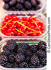 Berry fruits at marketplace - organic blueberries,...