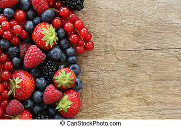 Berry fruits like strawberries, blueberries, red currants, raspberries and blackberries on a wooden board with copyspace