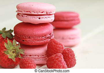Strawberry and raspberry macarons on a white table with fresh fruits