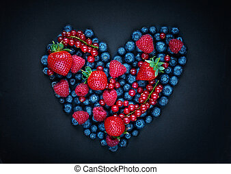 Berry mix fruits in Heart shape on black background. Assorted berries - Strawberry, Raspberry, Red currant, Blueberry and Blackberry. Love, Healthy concept