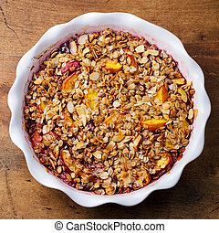 Berry, peach crumble, crisp in a baking dish. Wooden background. Top view.
