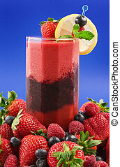 A glass of layered berry smoothie surrounded by fresh fruits (strawberryraspberryblueberry)