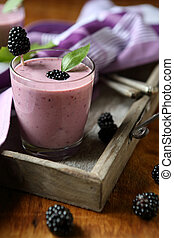 berry smoothie in a glass on a tray, sweet beverage