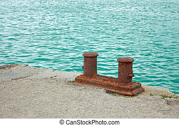 Steel rusty dual mooring bitt on a fragment of old concrete pier on the background turquoise sea water