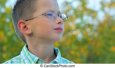 bespectacled boy stands against trees