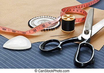 Still life photo of bespoke suit making equipment including tape, chalk, thread, scissors and pins on a pinstripe woolen piece of fabric.