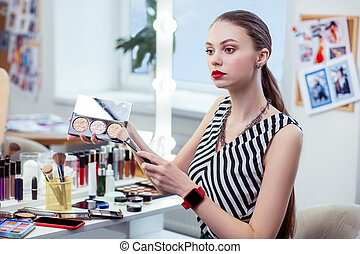 Pleasant beautiful woman holding her powder palette