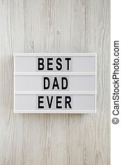 'Best dad ever' words on lightbox over white wooden background, top view. Overhead, from above, flat lay.