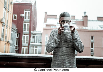 Pleasant nice man enjoying his hot tea