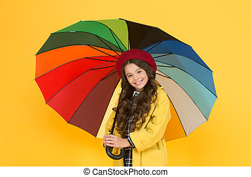 Best fashion choice. Happy child with fashion rain accessory on yellow background. Little girl hold rainbow colored fashion umbrella. Autumn look of small fashion model. Back to school