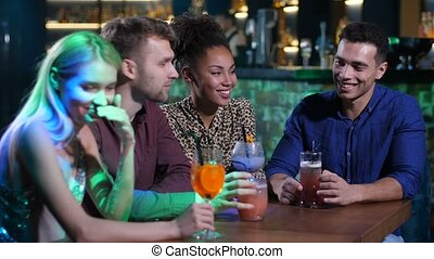Best friends chatting at bar table with drinks
