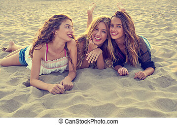 Best friends girls at sunset beach sand smiling happy...