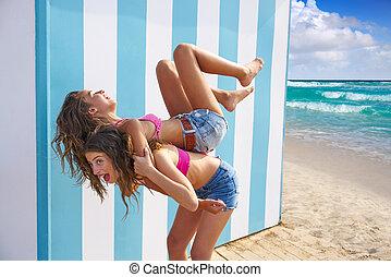 Best friends girls piggyback in summer beach with blue...