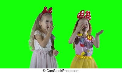 Best friends girls send air kisses at camera and embrace huge. Chroma key green screen background.