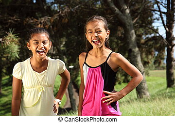 Two young school girl friends share a hilarious moment together while in the park in the sunshine