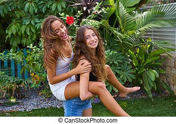 Best friends teen girls piggyback on backyard garden happy...