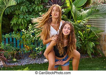 Best friends teen girls piggyback on backyard