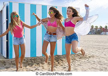 Best friends teen girls running happy in beach