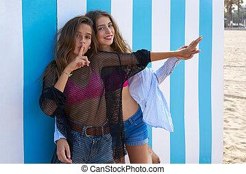 Best friends teen girls silence finger gesture in a summer...