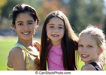 Three pretty girls of different ages and races smiling