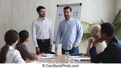Best male company employee being rewarded appreciated at team meeting, happy businessman ceo manager handshake promote praise intern get applause in office, staff award, recognition at work concept