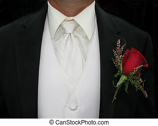 close up of white vest and black tuxedo with red rose boutonniere