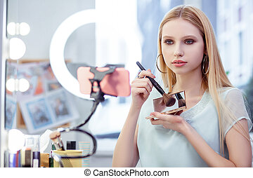 Pleasant young woman showing her cosmetics on camera