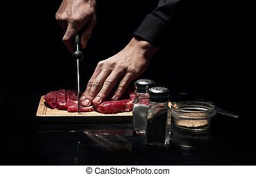 Close up of chefs hands chopping meat