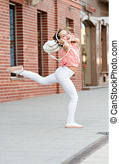 Best street dancing ever. Energetic little girl dancing with pleasure. Listening dancing music. Adorable dancer moving to music on city street. Small child enjoy dancing to modern music