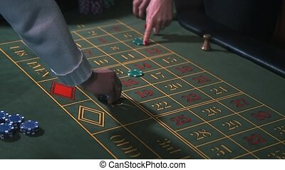 Betting chips - Casino Roulette People playing Roulette. Close-up only hands