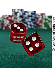 Two red dices rolling over a green felt. Out of focus stack of colorful chips on the background.