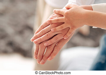 Hands of three generations being held together