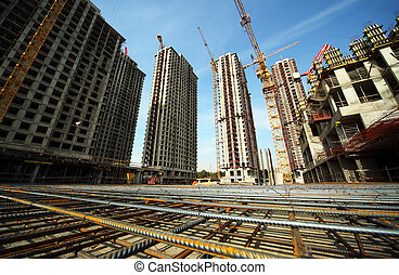 Between tall buildings under construction and cranes under a blue sky