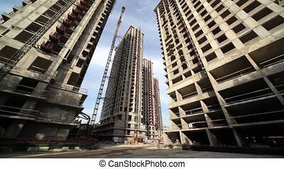 Between tall buildings under construction and cranes