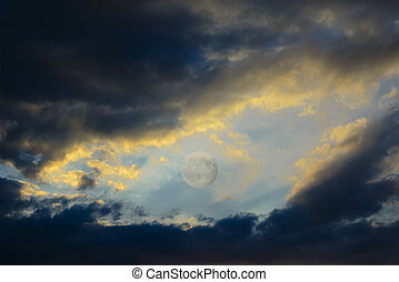 Between the dark clouds backlit by the sunset there is the full moon